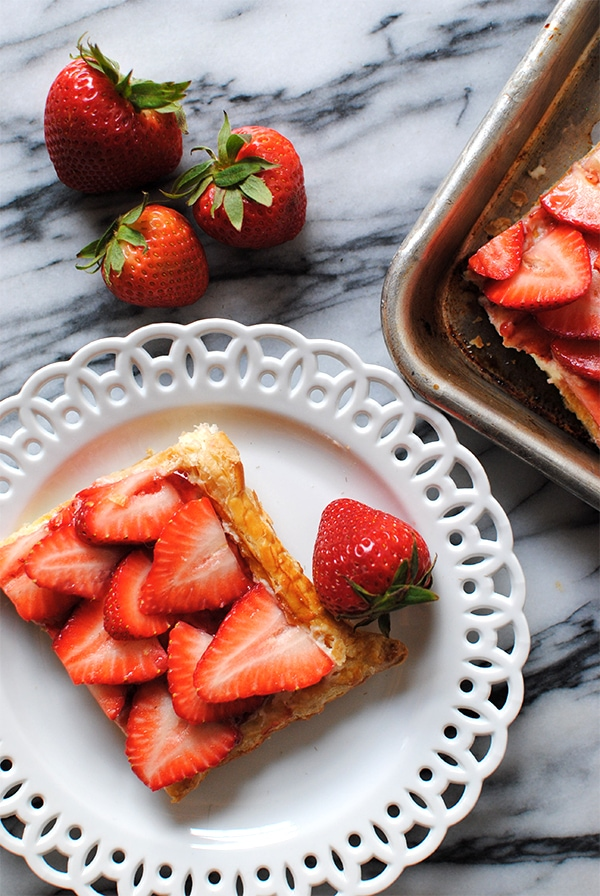 Slice of simple Strawberry Tart on a white plate with other strawberries
