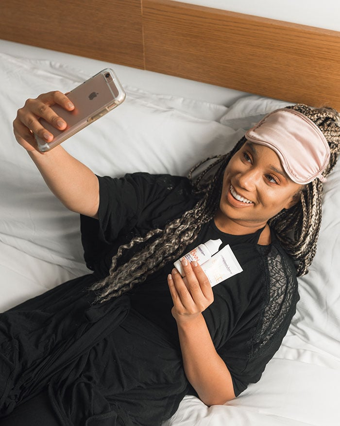 how to take your own passport photos - woman in bed taking selfie