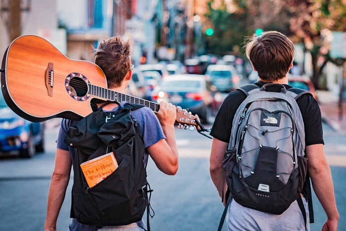 what is a hostel - two travelers walking with a guitar