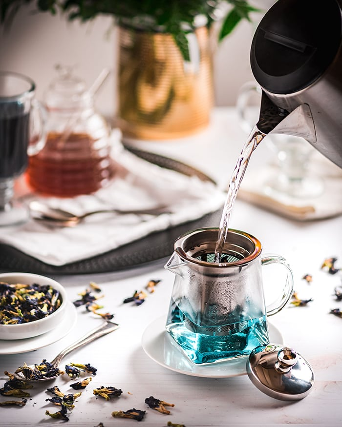 Butterfly Pea Flower Tea Latte - pouring hot water over tea leaves in teapot
