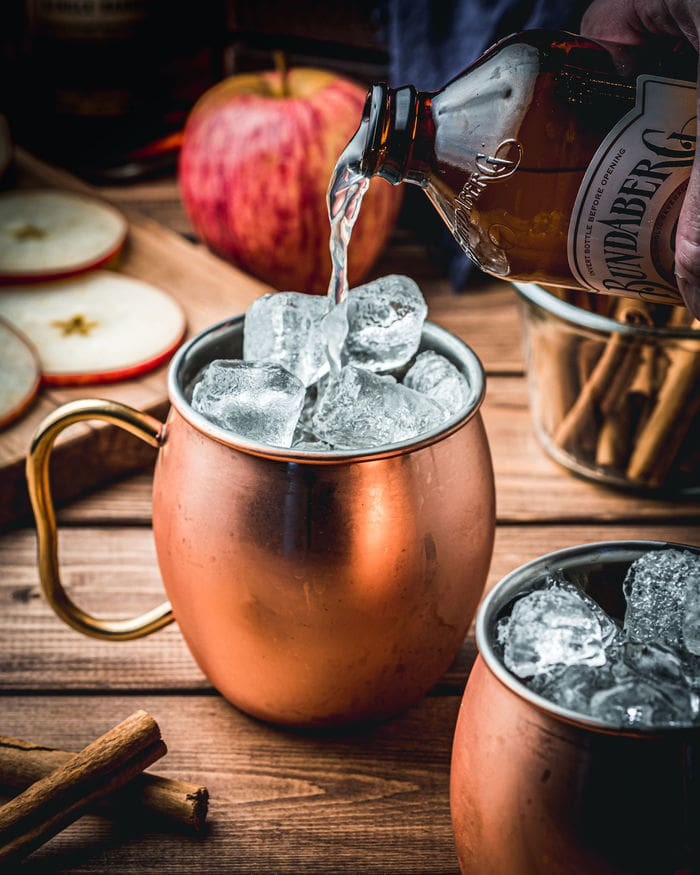 Apple Cider Mules - pouring ginger beer into copper mug