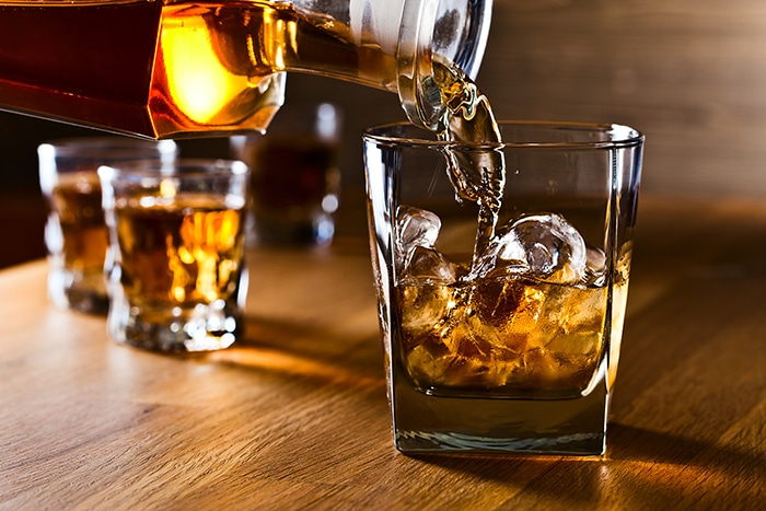 What is the Difference Between Bourbon and Whiskey - pouring into glass